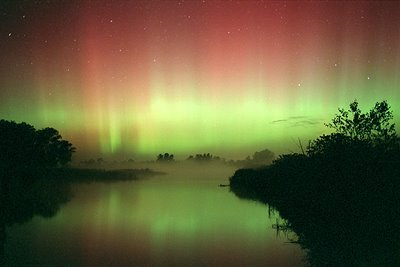 A beautiful aurora borealis forms when electrons collide with atoms of the upper atmosphere