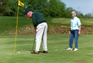 Old professor and wife golfing