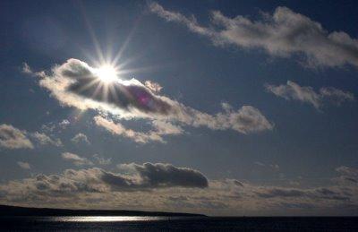 sun peeking through the clouds over water