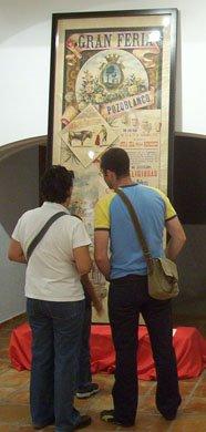 Visitantes de la exposición contemplan el cartel de 1901