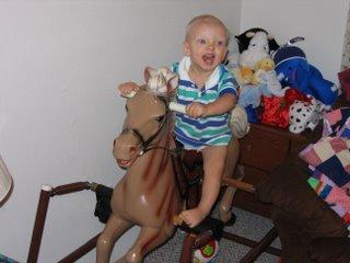 Matthew smiling on a rocking horse