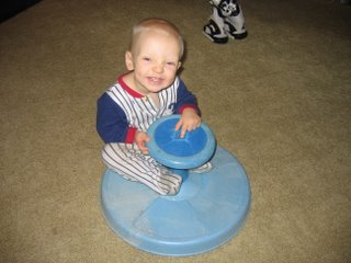Matthew smiling at the camera while on a spinning toy