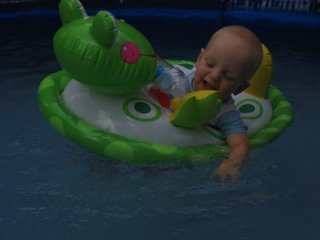 Matthew laughing while floating in a pool toy