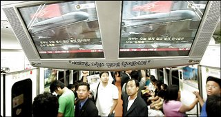 In Seoul, passengers on a subway train watch TV screens broadcasting North Korea's test launches.