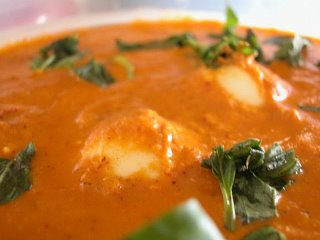 Egg curry garnished with basil