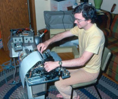 Thomas Kraemer in 1977 using a torn apart Model 33 Teletype hooked up via a serial current loop to an SC/MP microprocessor board