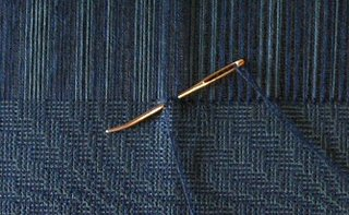 Hemstitching with a blunt bent point needle.