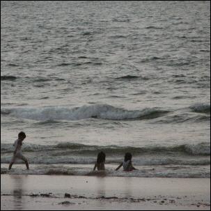 Lapset leikkivät rantavedessä Goan uimarannalla