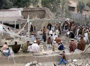 Pakistani tribesmen search a house that was destroyed after an airstrike in Damadola, January 14, 2006. REUTERS/Ali Imam