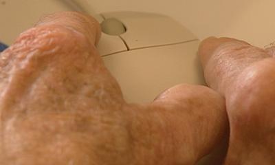 mãos de um idoso utilizando o mouse com dificuldades