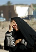 BAM, IRAN: A woman despairs sitting among the rubble in the earthquake stricken city of Bam, 04 January 2004. As many as 30,000 people are feared dead after the earthquake mostly levelled the town on 26 December 2003. Photo credit ODD ANDERSEN/AFP/Getty Images