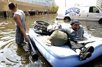 Finding refuge - August 30: Leeland Martin (left) pulls his brother, Milton, to the shelter in the Louisiana Superdome in New Orleans. Photograph: John Rowland/AP