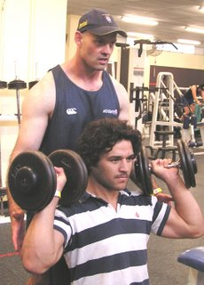 Martin Harland supervising Daniel Halangahu on the dumbbell press