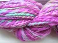skein of homespun yarn, mainly pink with some beige and turquoise