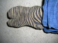 India's feet modelling brown/sand coloured stripy handknit socks