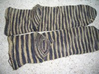 brown/sand soloured stripy handknit socks showing variation in stripe pattern between the two