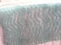 petrol blue  handknit shawl in progress, draped over radiator so wave pattern can be seen