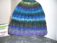 image of knit 2 purl 2 ribbed hat in stripy Noro yarn - mostly blues stripes with some purple and green
