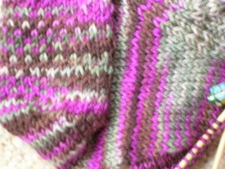 close up of handknitted sock heel in slip-stitch pattern. Coclour - browns, pinks, khaki green