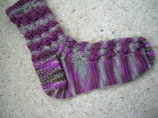 photot of one handknit sock in pinks, browns, greens