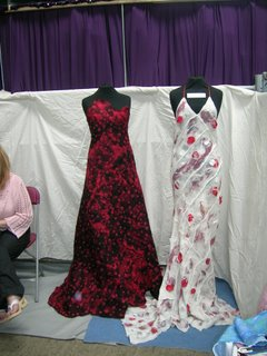 two long elegant felted dresses - one in white with red 'petals' scattered on it, the other red
