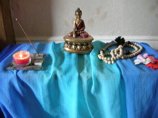 shrine with rupa, incense, candle, flower, beads