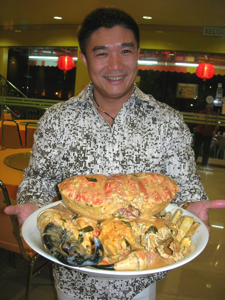 Restaurant Owner Marcus Proudly Posing With The Specialty King Crab