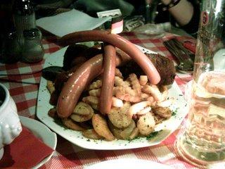 Un plato de salchichas con una banderita alemana