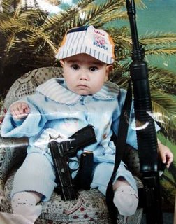 Picture: A Palestinian baby made to pose holding a gun and a rifle