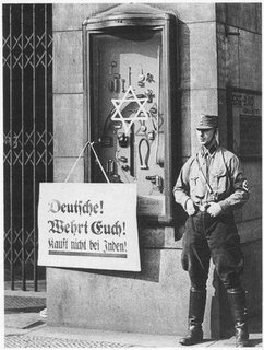 Picture: Nazi soldier standing in front a Jewish shop, with a sign not to buy from the Jews.