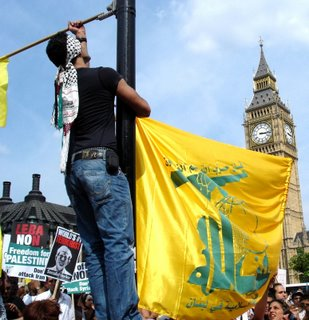 Picture: Kefiyyeh-wearing protestor hanging a Hizbullah flag in front of the Big Ben, August 5, 2006