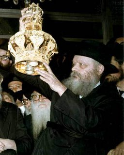 Rebbe-G-d-Almighty placing the crown on the Torah (5 books of Moses) scroll during the traditional Torah reading ceremony.