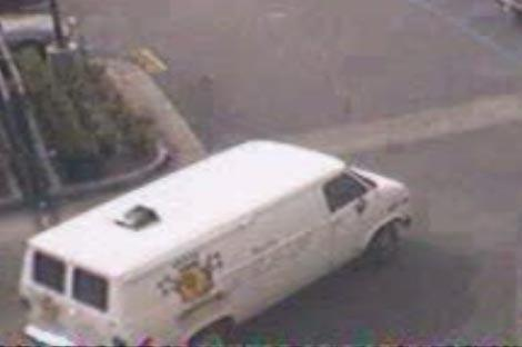 Suspects getaway vehicle - a white cargo van, unknown license, has unknown logo on its right and rear sides.