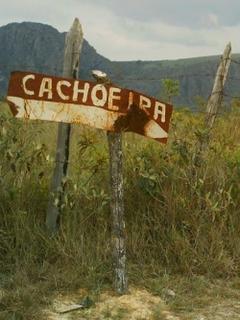 Uma placa enferrujada, perdida no meio do nada, indica: cachoeira