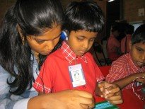 Krithika, Ms. Muktha's niece, helps with the braille tutor.