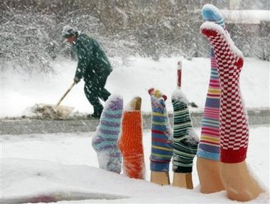 Photo of mannequin legs wearing colorful socks, buried updside down in a snow drift in Poland