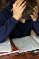 Teen boy at desk, poring over books and papers: head in hands