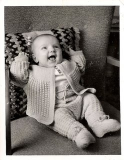 Extravagantly joyful baby with arms upraised