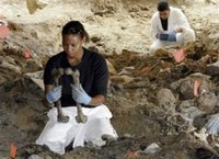 Forensic experts Sharna Daley of London, front left, examines two bones to find out whether they belong to the same person during exhumation at the mass grave site in the village of Kamenica, in the outskirts of the eastern Bosnian town of Zvornik, 120 kms north of Sarajevo on Wednesday, July 5, 2006. The mass grave in Kamenica is considered to be a secondary mass-grave, where bodies initially buried elsewhere were dumped, and containing around 300 bodies of Srebrenica massacre civilians. (AP Photo/Amel Emric)