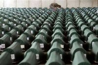 A man searches through more than 600 coffins with remains of victims of Srebrenica massacre waiting for the funeral in a factory hall in Potocari on July 11, 2005. REUTERS/Danilo Krstanovic