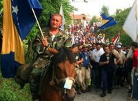 A Bosniak (Bosnian Muslim) man on horseback carries a Bosnian state flag at a start point of a four-day march to Srebrenica, in the village of Nezuk near Zvornik, 120 kms north of Sarajevo on Friday, July 7, 2006. Hundreds of Bosniaks (Bosnian Muslims) began a four-day march Friday along the route survivors used 11 years ago to escape the Bosnian Serb killings in Srebrenica, the worst massacre in Europe since World War II. (AP Photo/Almir Arnaut)
