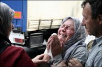 A Bosnian Muslim woman cries while praying for dead relatives in the streets of the Bosnian capital 8 July as the bodies of Srebrenica victims are transported by truck from a central Identification facility to their final resting place at a memorial centre in Potocari, near Srebrenica. Thousands of Bosnian Muslims were to mark the 11th anniversary of the Srebrenica massacre 11 July, with a ceremony including the burial of the remains of more than 500 victims of the slaughter(AFP/File/Elvis Barukcic)