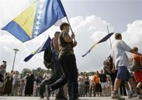 Bosnian people carrying Bosnian flags make their way to finish a four-day march to Srebrenica as they enter to the Memorial Center Potocari, near Srebrenica north of Bosnian capital Sarajevo, Monday, July 10, 2006. Hundreds of Bosnians began a four-day march on Friday along the route survivors used 11 years ago to escape the Bosnian Serb killings in Srebrenica, the worst massacre in Europe since World War II. March was a part of ceremony marking 11th anniversary of Srebrenica fall. Serb troops killed over 8,000 Muslim men and boys at Srebrenica in 1995, and most of the bodies are still missing. (AP Photo/Amel Emric)