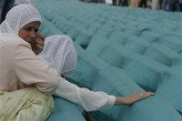 Bosnian Muslim women Zafa i Raza Delic, behind, is comforted by unidentified person as she weeps near the coffin of her father among the 505 bodies to be buried during funeral a ceremony at the Potocari Memorial Center, near Srebrenica north of Bosnian capital Sarajevo, Tuesday, July 11, 2006. (AP Photo/Amel Emric)