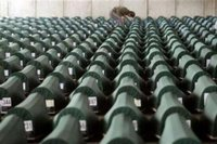 man searches through more than 600 coffins with remains of victims of Srebrenica massacre waiting for the funeral in a factory hall in Potocari on July 11, 2005. REUTERS/Danilo Krstanovic