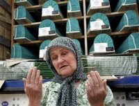 Rejha Ademovic, 60, a Bosnian Muslim woman from the eastern Bosnian town of Srebrenica, prays Saturday, July 8, 2006, in Sarajevo, in front of the truck carrying the remains of victims, among them her 15-year old son, killed in 1995 in a massacre. The trucks loaded with the coffins of 505 newly identified victims of Europe's worst massacre since World War II stopped for a few moments in Sarajevo on Saturday to allow hundreds of people to pay tribute to their beloved ones. The bodies will be buried at Srebrenica on the 11th anniversary of the massacre on Tuesday. (AP Photo/Hidajet Delic)