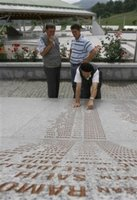 Unidentified Bosnian Muslim man points to the name of his relative on the marble stone with 8,370 names of Srebrenica victims written on it, at the Memorial Center of Potocari, near Srebrenica, north of Bosnian capital Sarajevo, on Sunday, July 9, 2006. Newly identified bodies will be buried in Srebrenica on Tuesday (July 11th) during the 11th anniversary commemorations of the massacre. Serb troops killed over 8,000 Bosniak men and boys at Srebrenica in 1995, and most of the bodies are still missing. (AP Photo/Amel Emric)