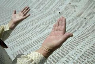 A Bosnian Muslim woman prays above a marble stone engraved with 8,370 names of Srebrenica massacre victims at the Memorial Center Potocari, near Srebrenica, July 6, 2006. About 500 identified victims of the Srebrenica massacre will be buried on its 11th anniversary on July 11, 2006. REUTERS/ Danilo Krstanovic (BOSNIA AND HERZEGOVINA)