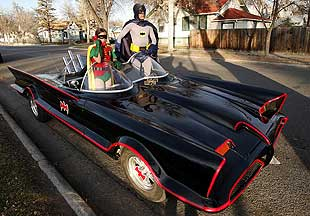 Clint Young, as Batman, and Austin Moore, as Robin, pose with a replica of the original Batmobile. Young makes and sells the cars.