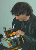 Neil Gaiman signs a stack of Sandman Books in 2006 at The Science Fiction Museum and Hall of Fame
